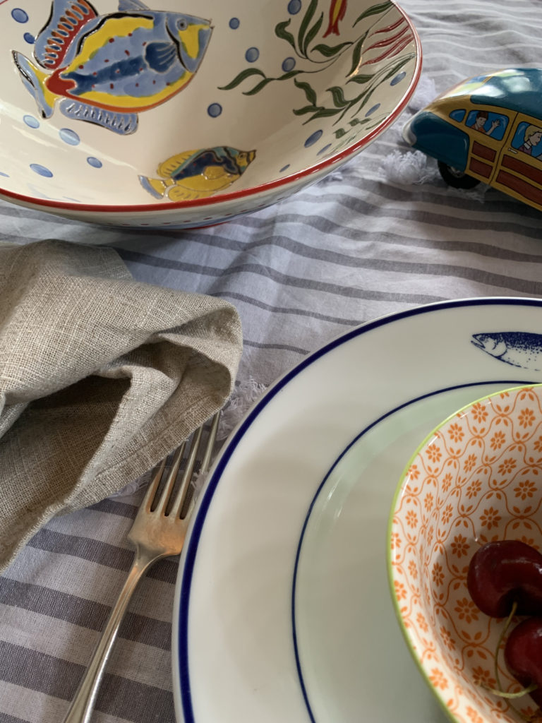 place setting on tablecloth with fish bowl and tin car