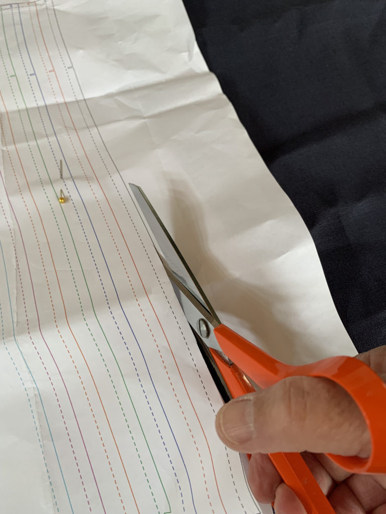 pattern piece pinned to navy linen fabric
